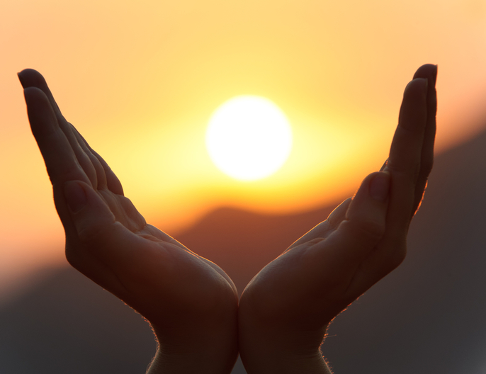 Hands cupped to hold distant sun setting over mountains