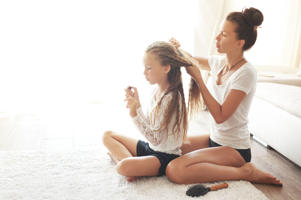 Young healthy mother combing daughter's hair