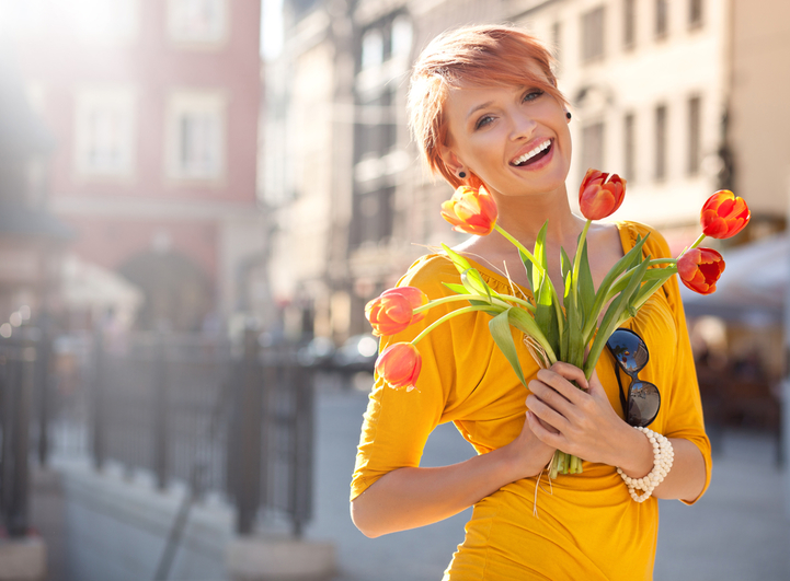 Smiling woman with bouquet of orange tulips