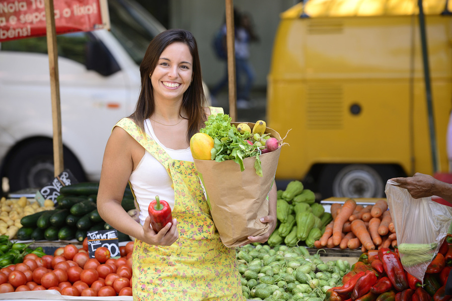 Smiling woman buying vegetables at farmers market