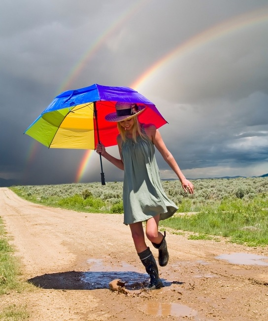 Young woman splashing in mud puddle with rainbow umbrella and rainbow arc in background