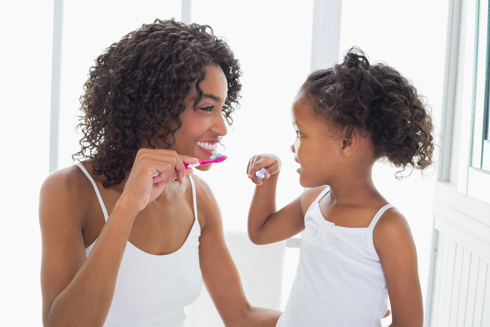 Young mother and daughter brushing their teeth
