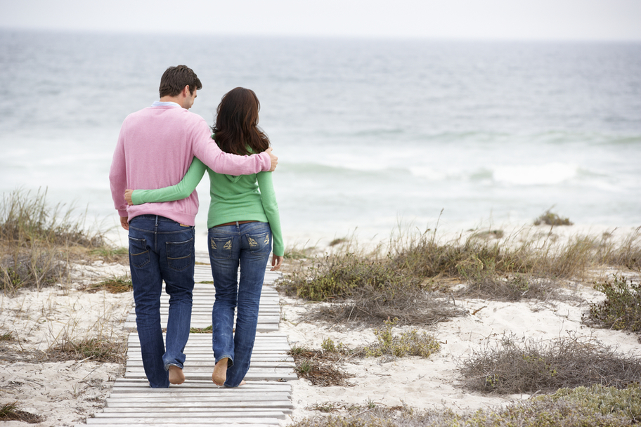 Man/woman couple walking on boardwalk at the beach
