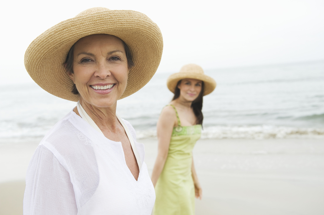 Smiling, confident, mature woman walking on beach with daughter