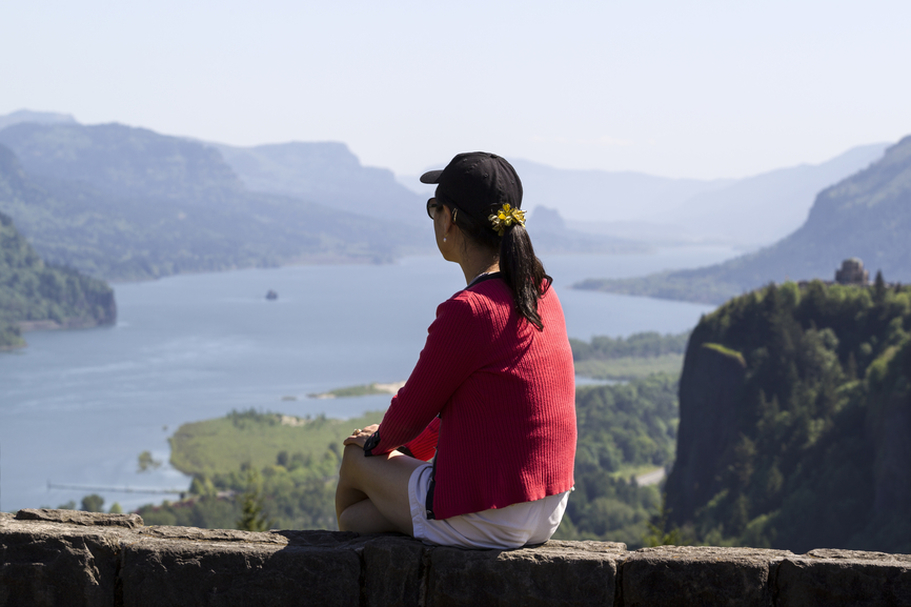 Woman sitting on stone wall overlooking a mountain lake