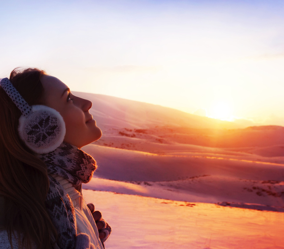 Young woman in mountain snow field enjoying winter sunset