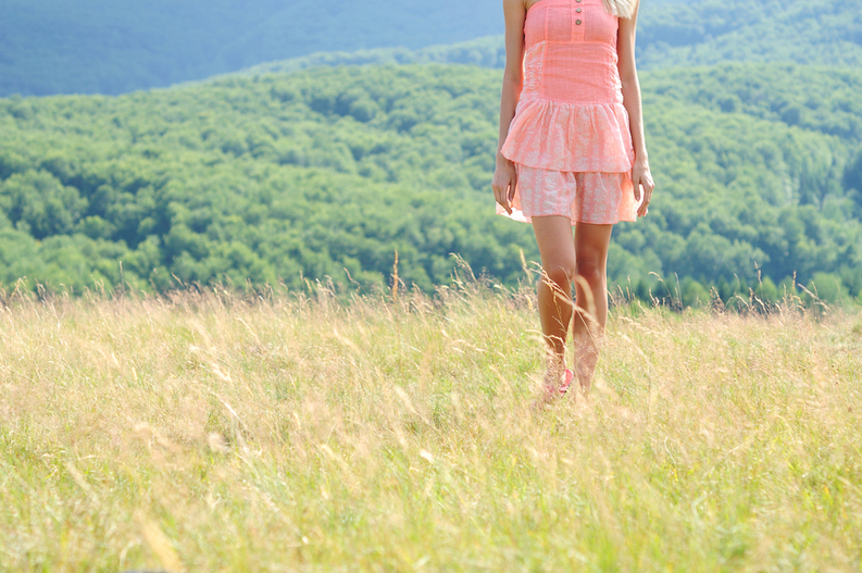 Woman walking in a summer meadow